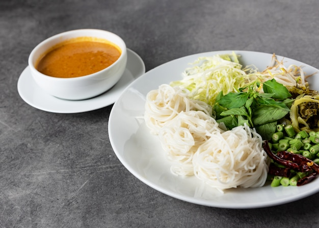 Rice noodles with fish curry sauce served with vegetables, kanom jeen nam ya traditional thai cuisine