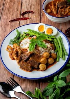 ビーフンにフィッシュカレーソース、ミートボール、鶏の血の立方体、鶏の足、ゆで卵、そしてたくさんの野菜をのせます。タイ料理、タイはそれを「カノム・ジーン・ナム・ヤ」と呼んでいます。お料理を美しく飾ってお召し上がりください。