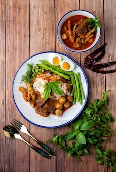 생선 카레 소스를 곁들인 쌀국수, 미트볼, 치킨 피 큐브, 닭발, 삶은 계란 및 많은 야채를 얹은 쌀국수. 태국 음식은