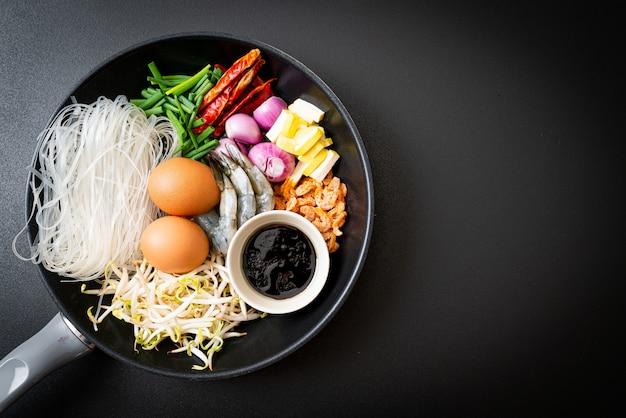 Rice noodles with ingredients in pan