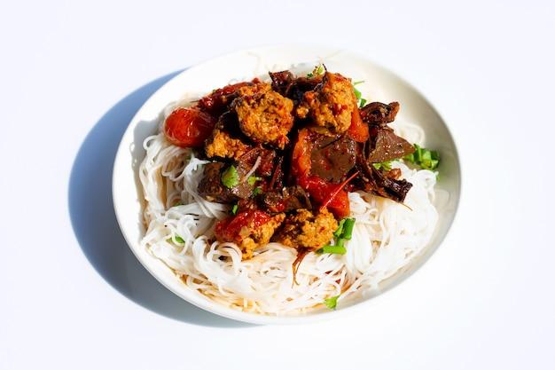 Рисовая лапша с северным тайским карри из свинины в белой тарелке на белом фоне.