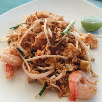 Рисовая лапша с креветками и овощами крупным планом на столе. вид сверху горизонтального