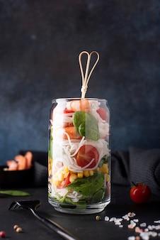Рисовая лапша с креветками и овощами в стеклянной банке на темном фоне, крупным планом