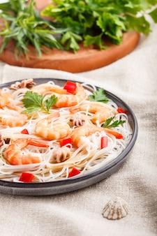 Рисовая лапша с креветками или креветками и маленькими осьминогами на серой керамической тарелке на белом льняном текстильном селективном фокусе