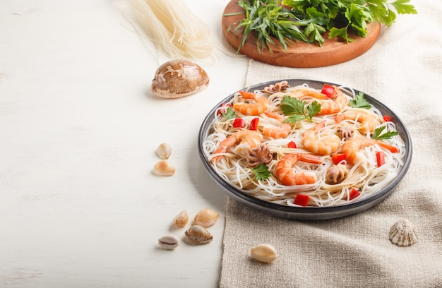 Рисовая лапша с креветками или креветками и маленькими осьминогами на серой керамической пластине на белом деревянном фоне. вид сбоку, копия пространства.