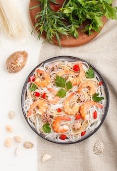 Рисовая лапша с креветками или креветками и маленькими осьминогами на серой керамической пластине на белом деревянном фоне. вид сверху, крупный план.