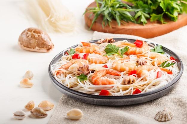 Рисовая лапша с креветками или креветками и маленькими осьминогами на серой керамической пластине на белой деревянной поверхности. вид сбоку, выборочный фокус.