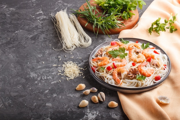 Rice noodles with shrimps or prawns and small octopuses on gray ceramic plate on a black concrete background