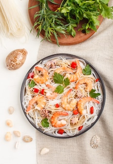 Rice noodles with shrimps or prawns and small octopuses on gray ceramic plate on a white wooden background. top view, close up.