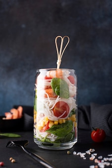 Rice noodles with shrimps and vegetables in a glass jar on a dark background, close-up
