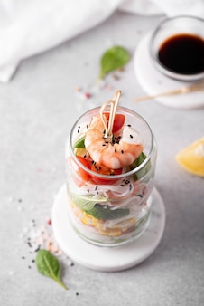 Rice noodles with shrimps and vegetables in a glass jar on a white table, top view