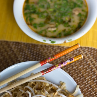 Rice noodles with sprouted soy and spicy soup tom yam with shrimps and greens