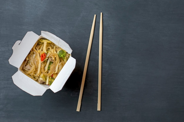 Rice noodles with vegetables and veal in a paper box with chopsticks on a black background