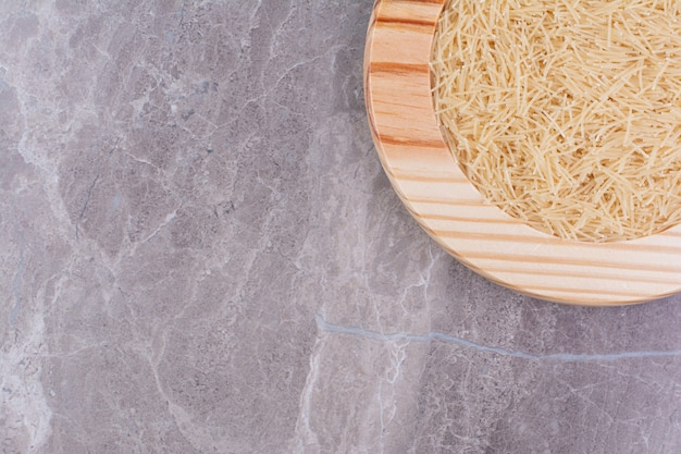 Rice noodles in a wooden platter on the marble