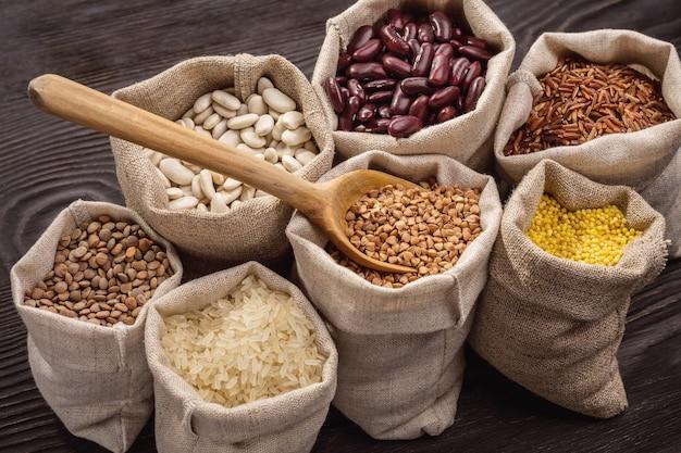가방, 나무 숟가락에 쌀, 완두콩, 콩 및 곡물. 확대.
