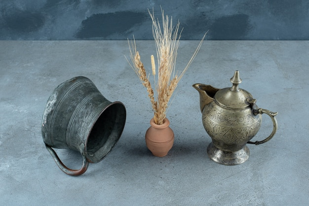 Rice plant with metallic kettle around on a blue background. high quality photo