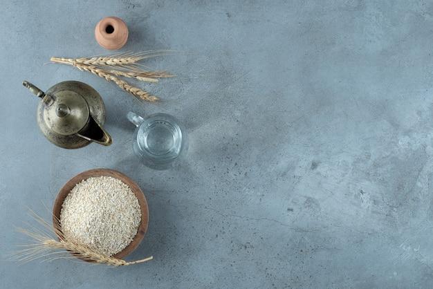 青い背景の周りに金属ケトルと稲。高品質の写真