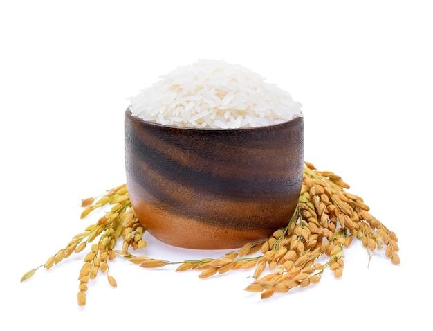米の植物、白い背景の上の木製のボウルにタイのジャスミン米の穀物