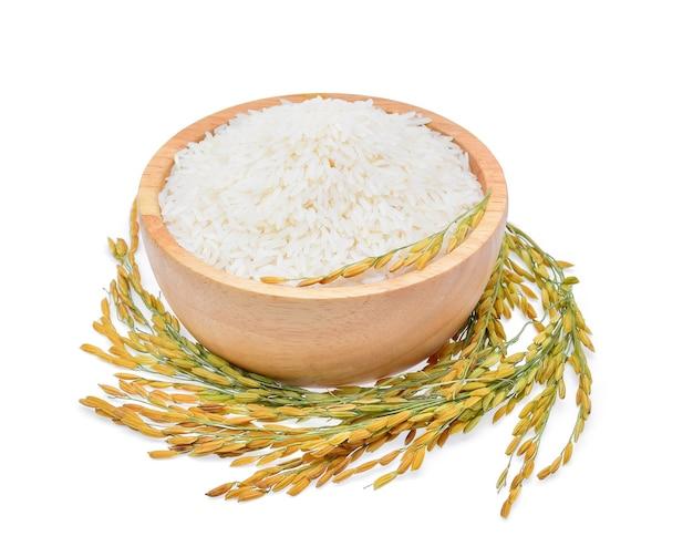 Рисовые растения, зерна тайского жасминового риса в деревянной миске на белом фоне
