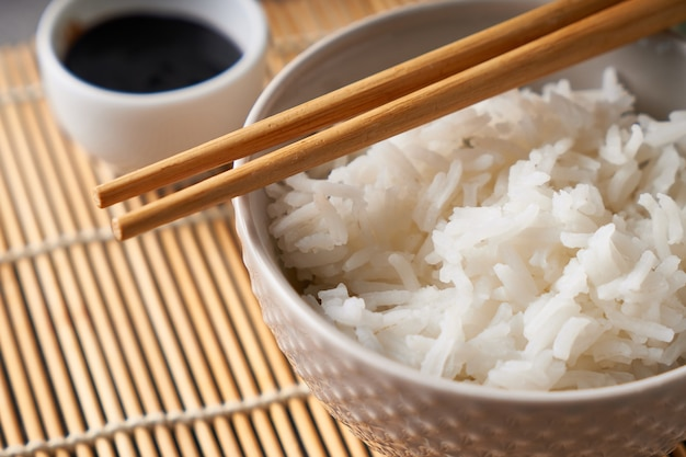 Rice in a porcelain bowl, with japanese chopsticks, soy sauce, served on a gray stone table close up