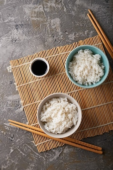 Rice in a porcelain bowl, with japanese chopsticks, soy sauce, served on a gray stone table copy space top view