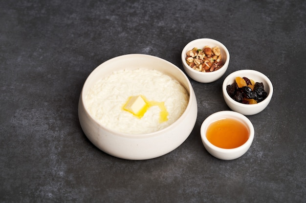 Rice porridge with milk, raisins, honey and nuts in a bowl.