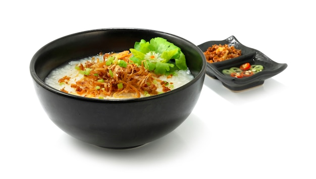 Rice porridge with shredded squids served crispy garlic and sour chilli sauce decorate vegetable sideview