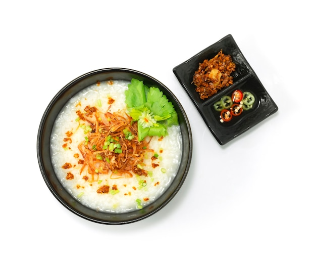 Rice porridge with shredded squids served crispy garlic and sour chilli sauce decorate vegetable topview