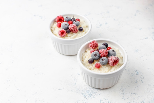 Rice pudding with frozen blueberries and raspberries in white bowl