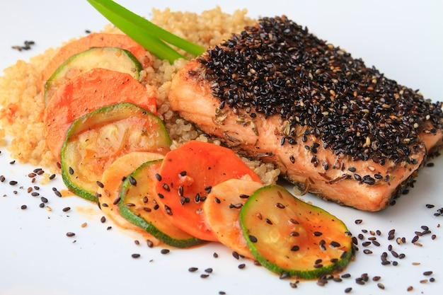 Rice, salmon and vegetables decorated with chia seeds served on a white plate