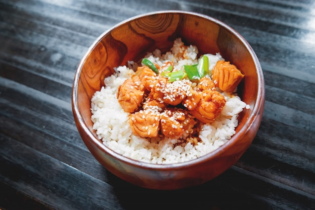 Rice in sauce with stir fried vegetables and salmon in wooden bowl