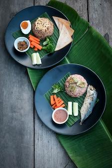 Приправленный рисом с креветочно-пастовым соусом, жареной скумбрией и ветчиной с курицей.