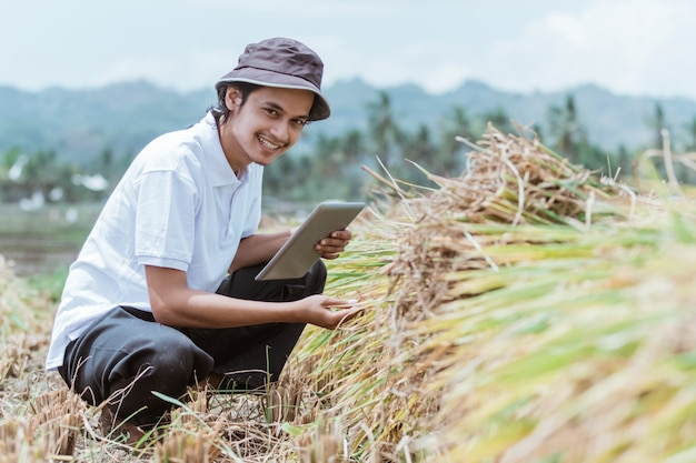 A rice seller in the rice fields smiles while holding a tablet while observing the harvest against the rice field