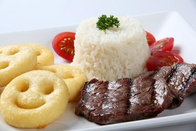 접시에 쌀, 스테이크, 감자 튀김.