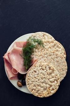 Рисовые тосты с ветчиной и оливками на белой тарелке