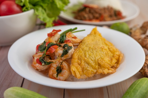 Rice topped with shrimp and omelet on a white plate.