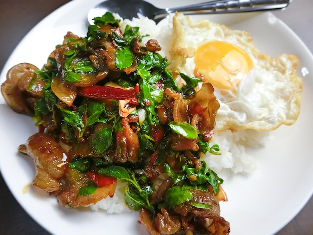 Rice topped with stir-fried bacon pork and basil and fried egg in a white dish