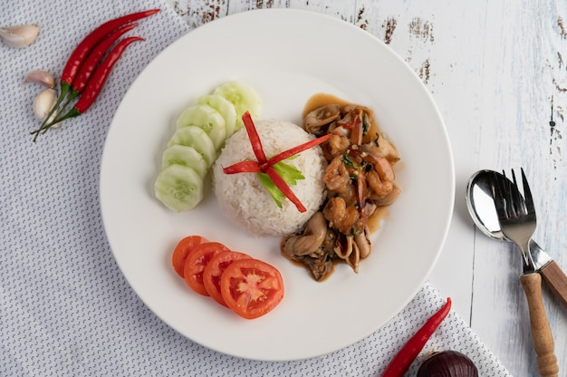 Rice topped with stir fried basil with squid and shrimp