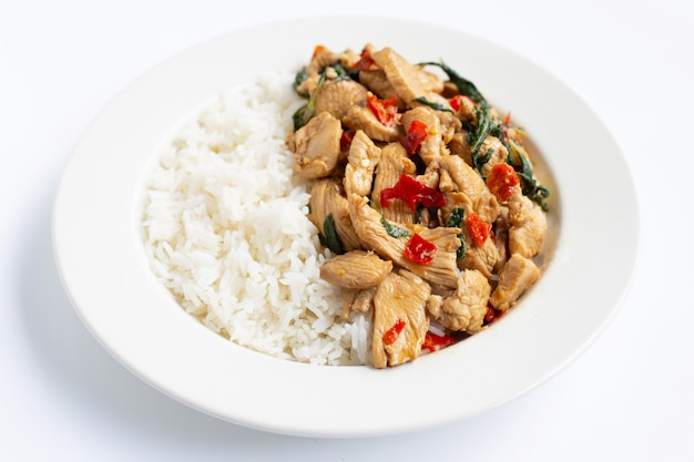 Rice topped with stir-fried chicken and holy basil on white