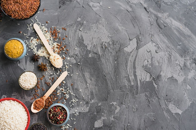 Rice; turmeric powder; star anise and peppercorn on black weathered backdrop with space for text
