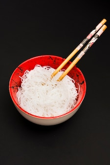 Rice vermicelli in bowl with chopstick over black surface