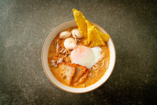 Rice vermicelli noodles with meatball, roasted pork and egg in spicy soup - tom yum noodles
