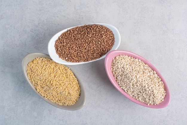 Rice, wheat and buckwheat in bowls on marble.