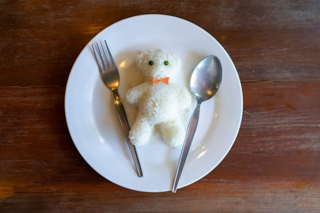 Rice in white plate docurated like bear doll on wooden table