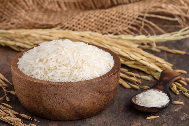 나무 배경에 나무 그릇에 rice.white 쌀(태국 자스민 쌀). 나무 테이블에 그릇에 재스민 쌀과 삼베 자루
