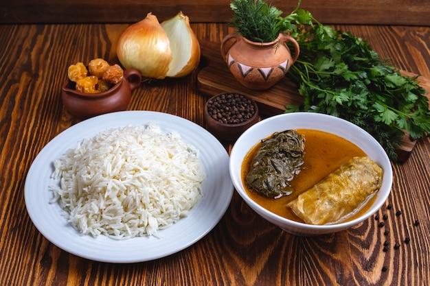 Рис с капустным рулетом зелень лук специи вид сбоку