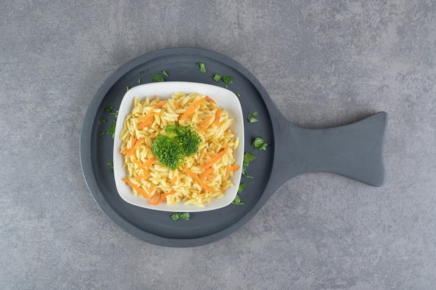 Рис с ломтиками моркови и брокколи на белой тарелке. фото высокого качества