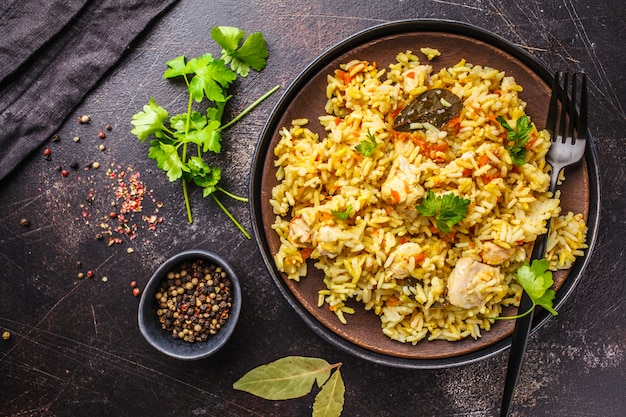 Rice with chicken in a black plate on a dark background, top view.