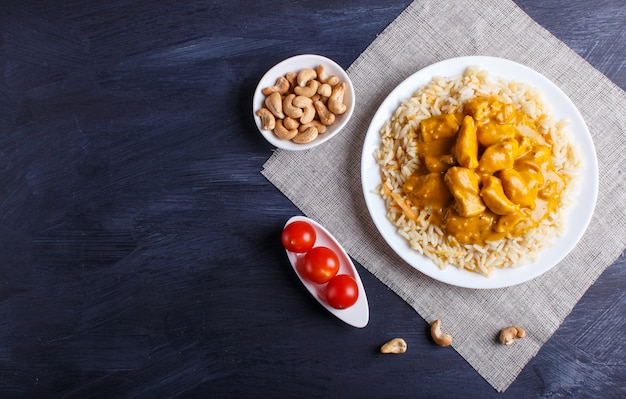 Rice with chicken curry sauce with cashew on black wooden surface.