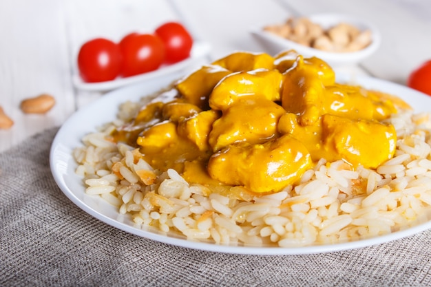 Rice with chicken curry sauce with cashew on white wooden background.